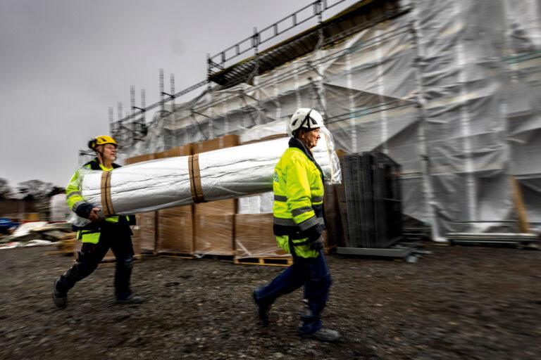 Full fart! Materialet är väldigt lätt. Ventabs Bo Sjöfjord och Bo Malmström har bråttom. I bakgrunden den helt inplastade förskolan Hoppet. Foto: Sören Håkanlind